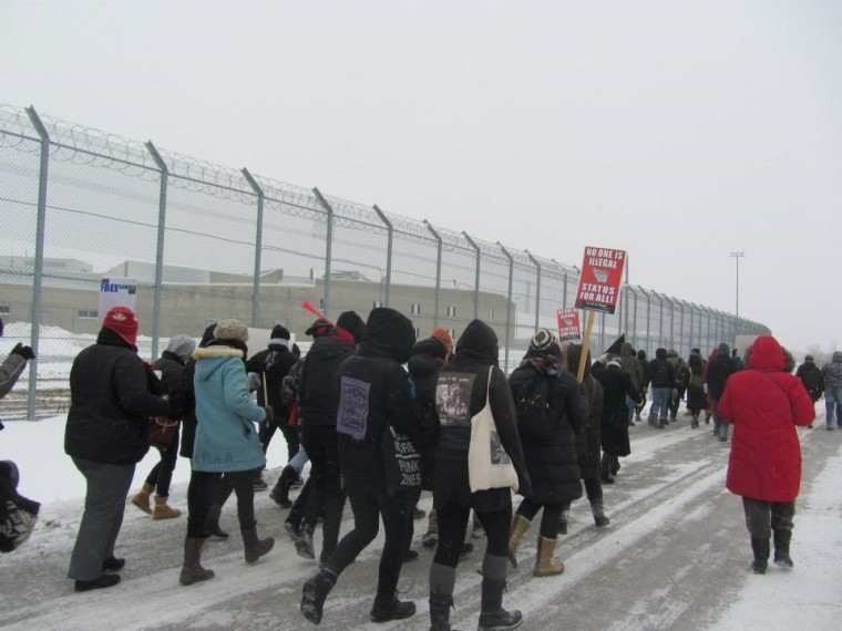 people marching at a rally against migrant detentions