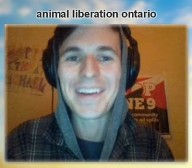 A person is smiling at the webcam, wearing headphones.